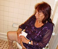 Very old woman undressing on toilet